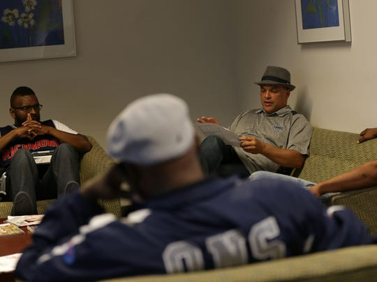 Neighborhood Change Agents Joe McCoy, from left Charles Muhammad, Office of Neighborhood Safety director DeVone Boggan and James Houston discuss the days agenda before heading out to engage fellows on the streets of Richmond, CA who are part of the Office of Neighborhood Safety on July 14, 2016.