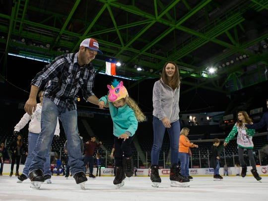 Weston Guy (left) catches 6-year-old Madison Guy as they skate with Peyton Pecskovszky during American Bank Center's Winter Wonderland Skating & Holiday Event on Thursday, Dec. 22, 2016.
