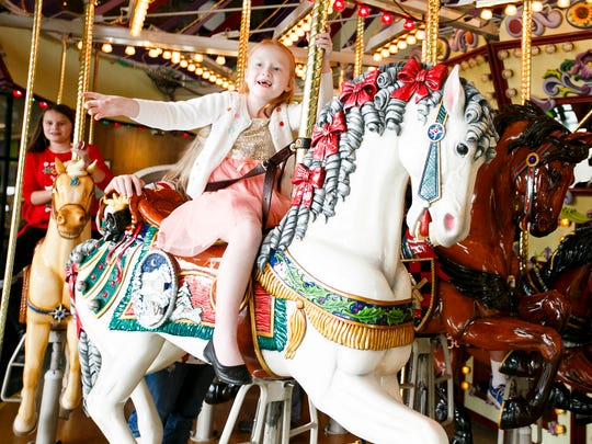 Grace Ball, 6, rides the Riverfront Carousel on Christmas Eve, Saturday, Dec. 24, 2016. The carousel will offer free rides from noon to 4 p.m. on Christmas Day and New Year's Day, with a suggested donation to support Marion-Polk County Food Share.