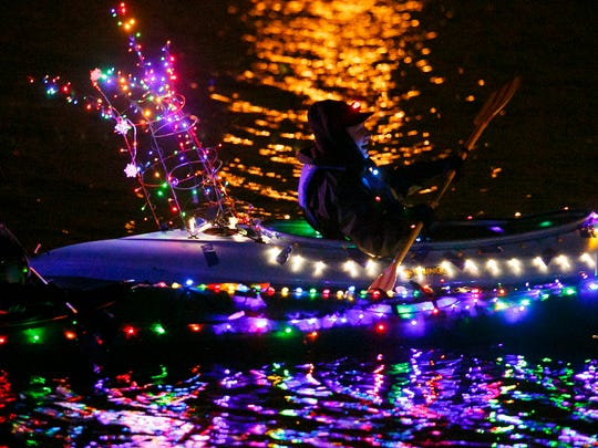 Karen Craven takes to the water with a tomato cage entwined in lights on the back of her boat at the Illuminata Regatta on the Willamette River in 2016.