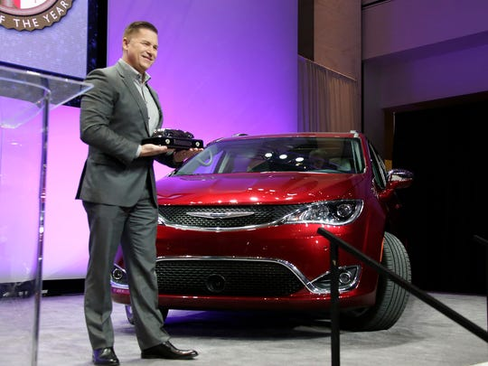Jim Kuniskis, head of Fiat Chrysler car brands, accepts the award for Utility Vehicle of the Year for the 2017 Chrysler Pacifica minivan at the North American International Auto Show on Monday Jan. 9, 2017 in the atrium at Cobo Center in Detroit.