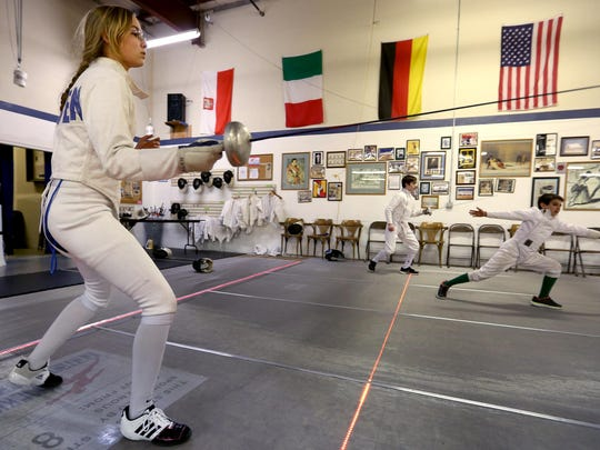 Olivia Merten (from left) of Corvallis, Ian Clingerman of Keizer and Justin Gonzalez of Salem warm-up at the Salem Fencing Club in March of 2015.
