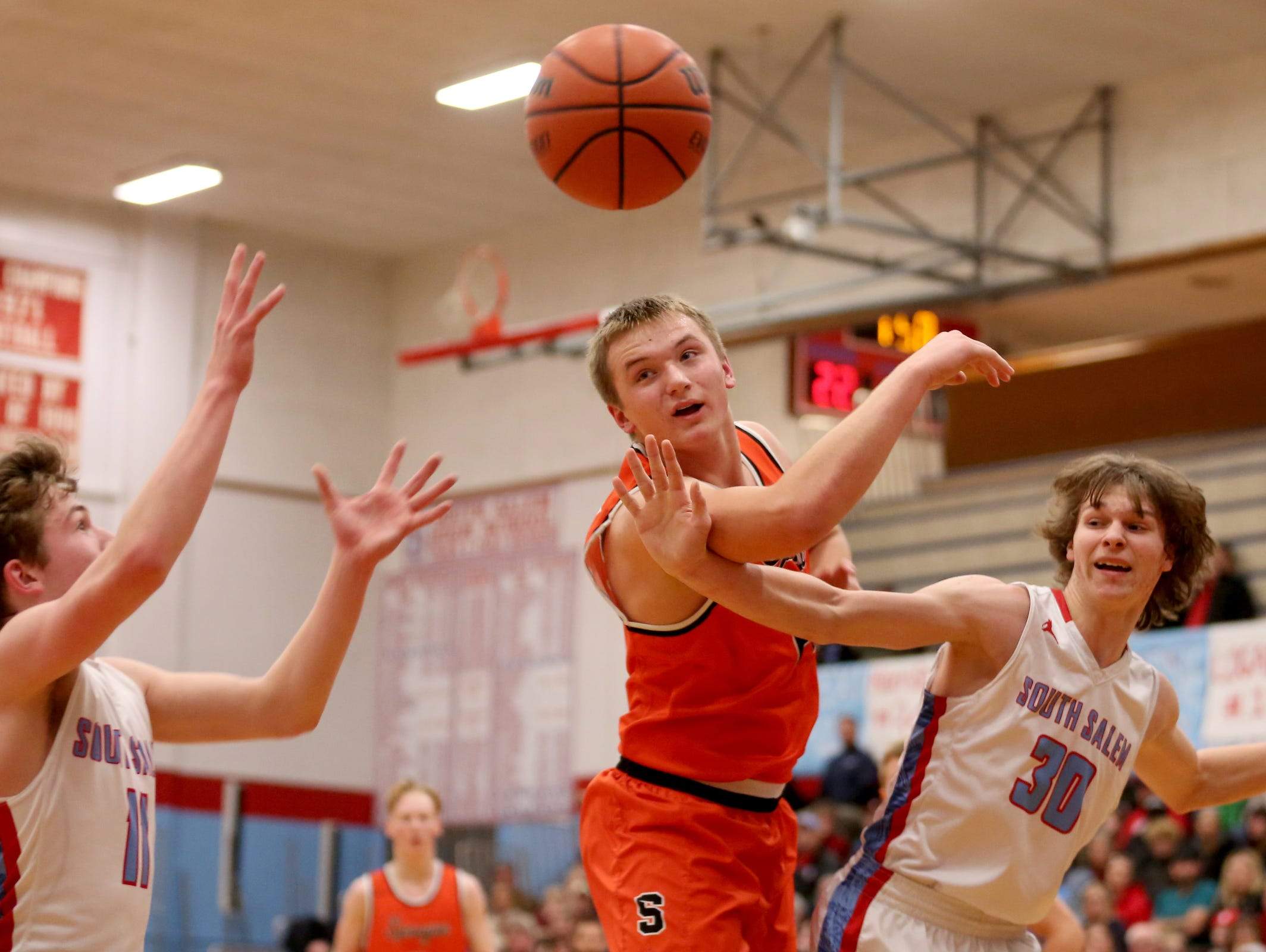 Sprague's Teagan Quitoriano (14) and South Salem's Tyler Wadleigh (11) and Ryan Brown (30) all reach for a rebound in the second half of the Sprague vs. South Salem boy's basketball game at South Salem High School on Friday, Feb. 3, 2017. Sprague won the game 64-58.