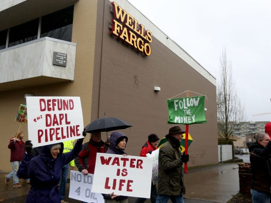 Dozens participate in a protest and march in downtown Salem urging four nationwide banks to defund the Dakota Access Pipeline on Saturday, Feb. 4, 2017. The protesters rallied outside the downtown Salem branches of Wells Fargo, U.S. Bank, Bank of America and Chase banks.