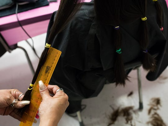 Haylie Goday has eight inches of her hair measured before being cut to be donated during John Paul II High School's A Cut Above hair donation event on Tuesday, Feb. 14, 2017.