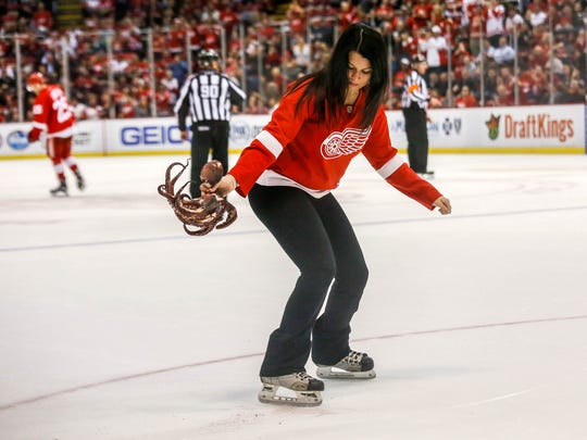 Maria Rotondo picks up an octopus that a fan through on the ice late in the third period of the Red Wings' 3-2 win over the Sabres on March 28, 2016 at Joe Louis Arena.