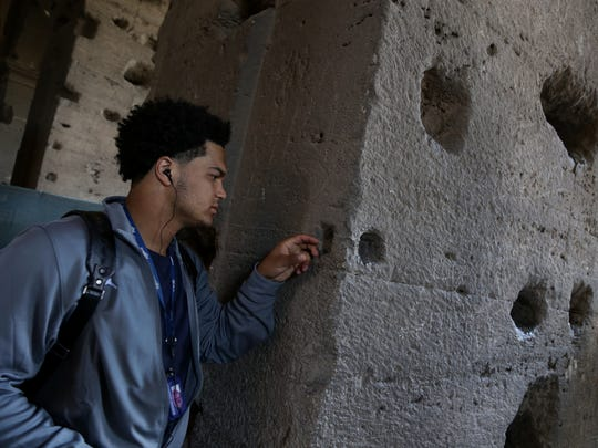 Michigan football player Carlo Kemp looks at the stones