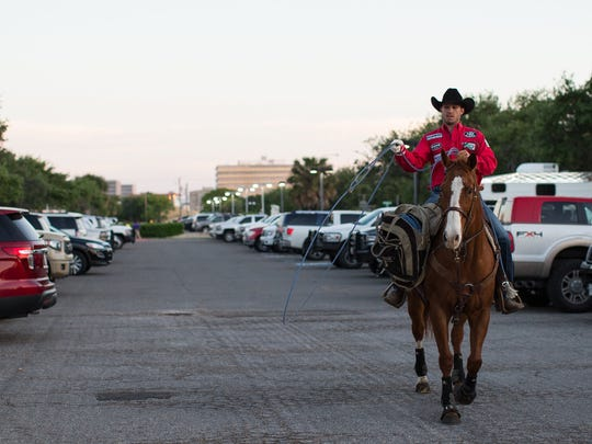 A cowboy practices roping as he rides thought parking lot of the American Bank Center on the first night of the Rodeo Corpus Christ, Thursday, April 14, 2016.