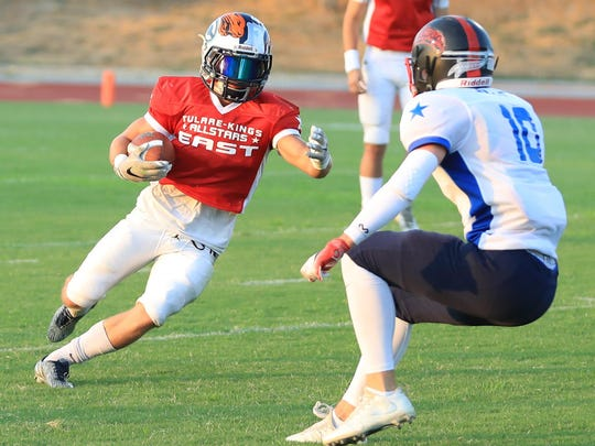 East's Connor Paden cuts inside of West's Mitchell Hunts during the East-West Tulare-Kings Counties All-Star Football Game at Groppetti Automotive Visalia Community Stadium.