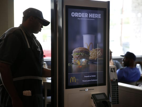 A member of the McDonald's staff makes an order on