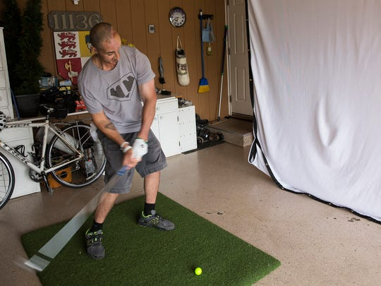 Tim McGrath of Sterling Heights, practices swinging with his golf simulator in the garage of his house, Wednesday, July 12, 2017 in Sterling Heights.