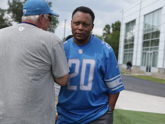 Barry Sanders is greeted as he walks onto the field