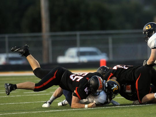 Solon's Tyler Linderbaum tackles Regina's Isaac Vollstedt during their game in Solon on Friday, Sept. 1, 2017.