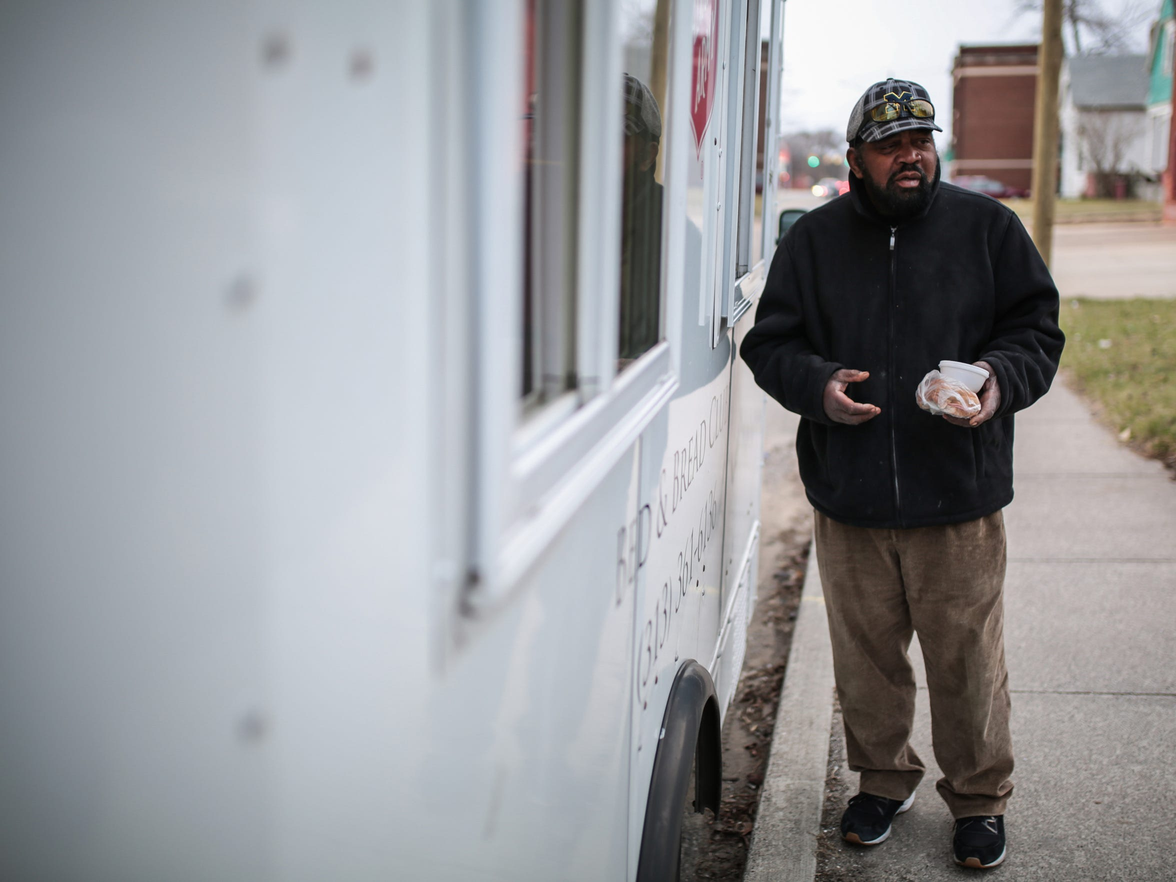 Darnell Taylor, 63, of Detroit receives a meal from the Salvation Army's Bed and Bread program food truck on Thursday, March 2, 2017, as he stands on Mt. Elliott on Detroit's east side. Taylor was once a local minister who operated three homeless shelters.