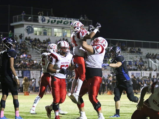Palm Springs' Jason Roberts (24) is lifted into the air by lineman Julian Polendo to celebrate a touchdown during the first half of the game against Cathedral City in Cathedral City on Friday night, October 6, 2017.