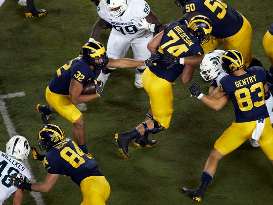 Michigan RB Ty Isaac (32) follows OL Ben Bredeson (74)