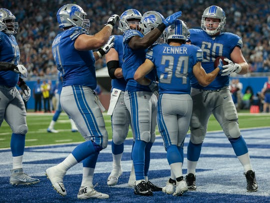The Detroit Lions celebrate a 1-yard touchdown by running