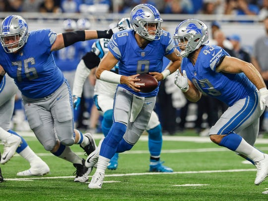 Matthew Stafford runs a play during the first half