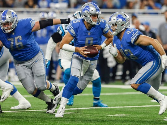 Matthew Stafford runs a play during the first half against the Carolina Panthers at Ford Field, Sunday, Oct. 8, 2017. Blocking for the Lions are T.J. Lang (76) and Nick Bellore (43).