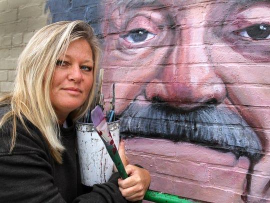 Pamela Bliss poses with her Kurt Vonnegut mural in
