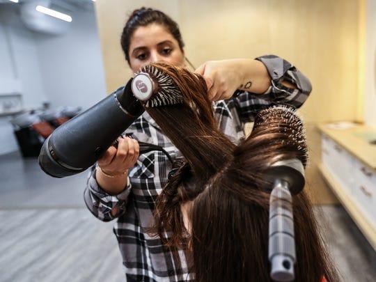 Katie Katz of Detroit gets a blowout from stylist Nina Nafa of Novi at the Detroit Blows.