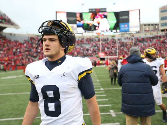 Michigan's John O'Korn leaves the field after the 24-10