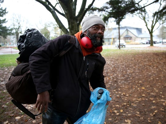 Preston Chambliss, 58, walks through Marion Square Park after receiving a sack lunch from the ARCHES Project Mid-Willamette Valley Community Action Agency in Salem on Thursday, Nov. 30, 2017.