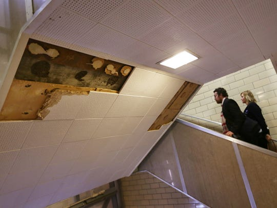 Pam Barnes, from right and Asher Huey of the American Federation of Teachers, walk by missing ceiling tiles while touring Osborn Collegiate Academy of Mathematics Science and Technology to look at some of the poor conditions that have prompted sickouts in DPS in Detroit on Thursday, Jan. 14, 2016.