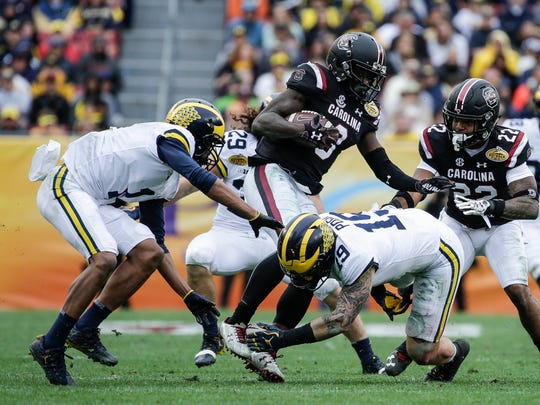 Michigan Wolverines defensive back Ambry Thomas (1), defensive back Jordan Glasgow (29) and defensive lineman Kwity Paye (19) try to stop South Carolina punt returner Chris Lammons in the first half of the Outback Bowl at Raymond James Stadium in Tampa, Fla., Monday, Jan. 1, 2018.