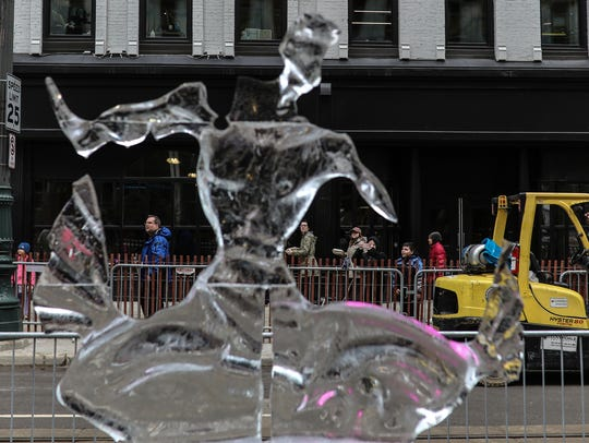 A ice sculpture of the Spirit of Detroit melts as people