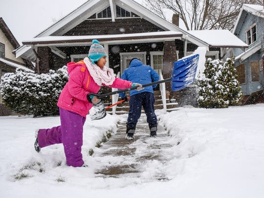 Nadia Donitzen of Detroit helps her uncle John Gordon of Detroit shovel snow in front of his house on Eason Street in Highland Park on Monday January 29, 2018. The temperature was in the 50s just days before.