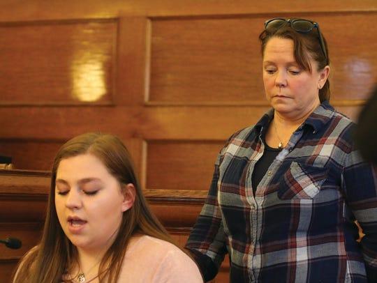 Rachel Johnson, left, reads a victim impact statement