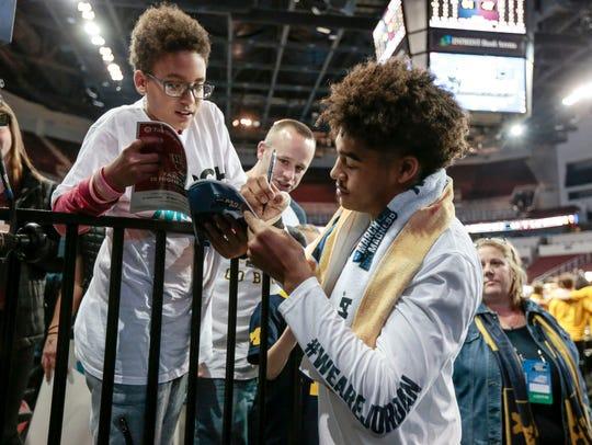 Michigan guard Jordan Poole signs autographs for fans