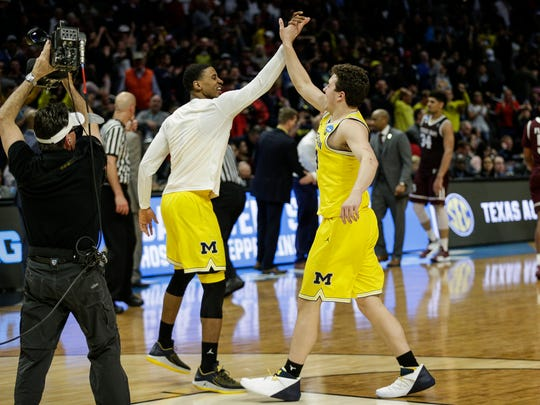 Michigan forward C.J. Baird (24), center, high-fives guard Charles Matthews (1) after U-M's 99-72 win over Texas A&M in the Sweet 16 of the NCAA tournament in Los Angeles on Thursday, March 22, 2018.