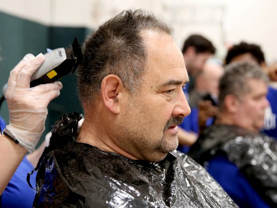 Mark Masters, 58, of Salem, gets a haircut during the