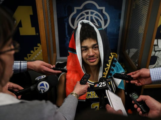 Michigan guard Jordan Poole talks to the media in the locker room after the title game loss.