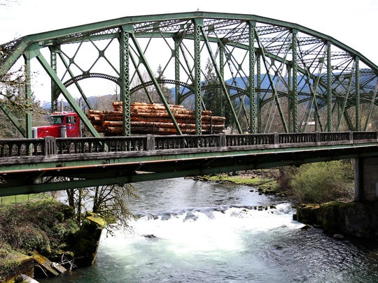 A log truck drives over Mill City's North Santiam River Bridge, which will be restored thanks to an $8.1 million federal grant.