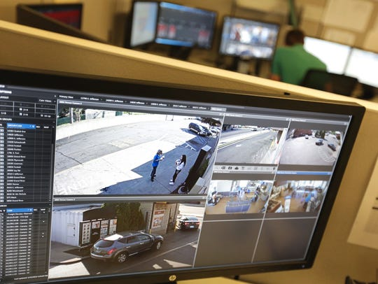 A crime analyst monitors video screens in the real