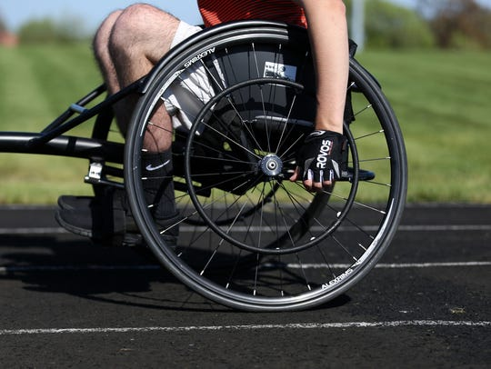 Owen Baker demonstrates the technique involved in competing on a race chair during track practice at Willamina High School on April 26, 2018.