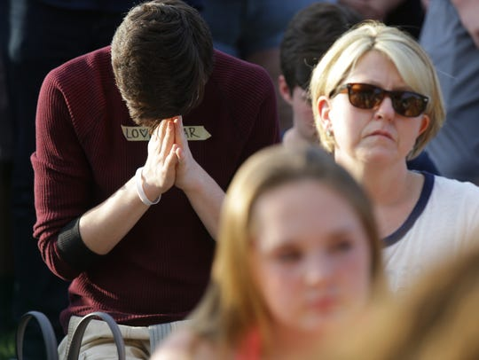 Students and parents pray at a prayer vigil held at