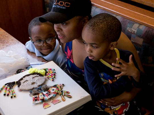 Jillie Fly, of Detroit, talks with another artist while sitting with her children Jerry Fly and Jacob Fly after showing her fabricated art doll during the Detroit Fine Art Breakfast Club at Noni's Sherwood Grille in Detroit on Monday, May 21, 2018. The meeting helps up-and-coming artists and community members connect with buyers and gallery members during the weekly event.