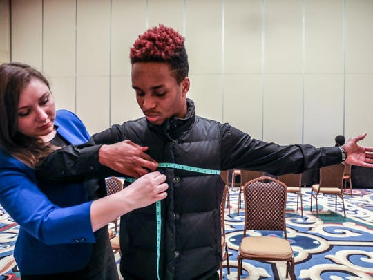 Najee Muhammad, 19, of Dearborn is measured for a uniform by Human Resources Coordinator Lauren Sharples as one of the last steps at the Allied Universal Security Services hiring event in May 2018 at Greater Grace Temple in Detroit.