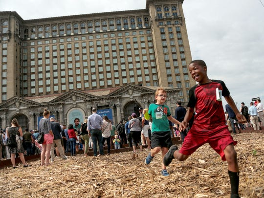 Jayden Perry, right, of Belleville and Jan Sauer of Bloomfield Township race while waiting for the start of Ford Motor Company's celebration at the Michigan Central Station in  Corktown, a Detroit neighborhood on Tuesday, June 19, 2018.