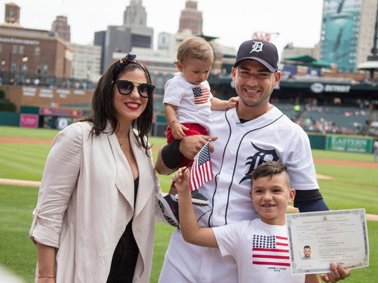 Arlene Iglesias poses with her fiance Detroit Tigers shortstop Jose Iglesias, who holds their 9-month-old Alvaro. Jose, 7, waves an American flag after his father and Leonys Martin were both sworn in as American Citizens in a special ceremony held at Comerica Park in Detroit on Monday, June, 25, 2018.