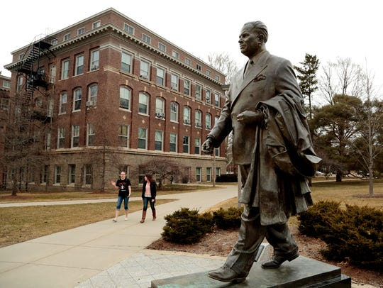 Students walk past the statue of John A. Hannah, MSU's