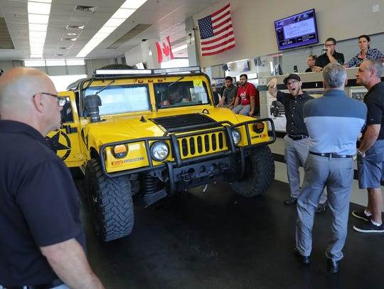 Car buyers make a bid on this Hummer on the auction