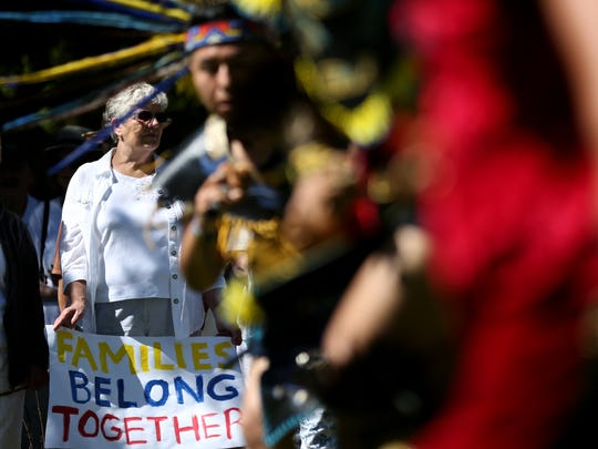 Jan Hentze, 72, of Salem, carries a sign as Titlakawan Aztec Danza performs during a Families Belong Together Rally, part of a nationwide series of protests against the separation of parents and children at U.S. borders, at the Oregon State Capitol in Salem on Saturday, June 30, 2018.