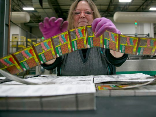 Packing line feeder Sue Johnson gets books of Texas $1 instant lottery tickets broken down to be shrink-wrapped and sent out after being printed at Pollard Banknote in Ypsilanti on Thursday, July 5, 2018.