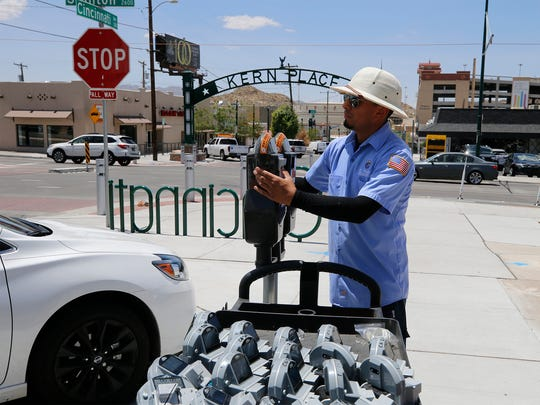 Chris Gamez of the International Bridge Park and Meter Department with the city of El Paso installs a parking meter mechanism in the Kern Place area along Cincinnati Street.