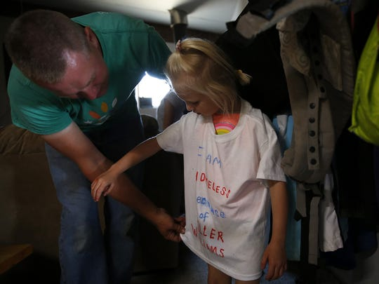 Travis Tubbs (left) puts a shirt on his daughter Tiana,